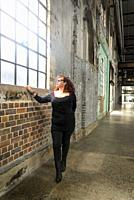 Woman dressed in black looking through a window in an industrial type of building.