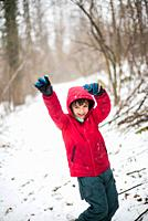 portrait of smiling child and arms raised to the sky with red hat in the snowy forest.