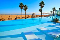 Resort infinity pool in the beach with palm trees paradise.