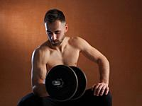Young man training with weight lifting.