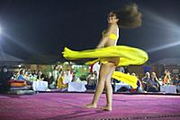 Belly dancer performing a traditional dance in the open air at night, near Abu Dhabi, United Arab Emirates, Middle East.
