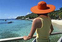 woman wearing a big orange hat sitting on balustrade at Basil´s bar, Mustique island, Grenadines islands, Saint Vincent and the Grenadines, Winward Is...