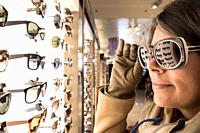 Woman Testing Sunglasses in Retail Store.