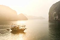 Sunrise over fishing boat in the karst landscape of Ha Long Bay, Quang Ninh Province, Vietnam. Ha Long Bay is a UNESCO World Heritage Site.