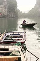 Vietnamese boatman in the karst landscape of Ha Long Bay, Quang Ninh Province, Vietnam. Ha Long Bay is a UNESCO World Heritage Site.