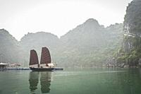 Vietnamese traditional boat in karst landscape of Ha Long Bay, Quang Ninh Province, Vietnam. Ha Long Bay is a UNESCO World Heritage Site.