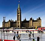 Parliament Hill Centre Block Peace Tower with afternoon sun on skaters on the Canada 150 Rink outdoors in winter Ottawa.