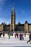 Parliament Hill Centre Block Peace Tower with afternoon sun on skaters on the free Canada 150 Rink refrigerated outdoor skating rink in winter Ottawa.