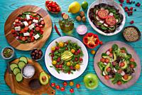 assortment of salads and healthy vegan ingredients on turquoise table.