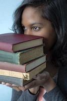 Young Hispanic woman holding a pile of books.