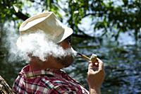 STOCKHOLM, SWEDEN Street scene. Hipster man smoking a corncob pipe.