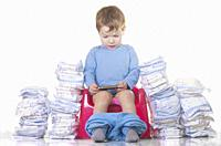 Baby boy sitting on chamber pot with smartphone and toilet paper rolls around. Potty training concept.