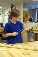 8th Grade Boy Using File in Technology Class, Wellsville, New York, USA.