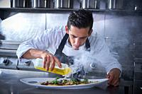 Chef preparing octopus recipe in kitchen with smoke and oil.