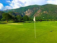 Golf Course Gerre Losone with Golf Green with Flag and Mountain in Losone, Ticino, Switzerland.