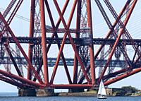 Sailing boat beside Forth Bridge (Forth Railway Bridge) crossing the Firth of Forth between North and South Queensferry,UK.