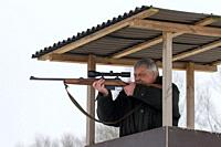 Big game hunter in raised hide aiming and shooting deer in forest during the hunting season