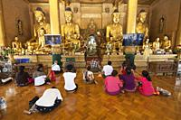 Devotees prying in the Temple with the Padamya Myetshin image of the Buddah, Shwedagon pagoda, Yangon, Myanmar, Asia.