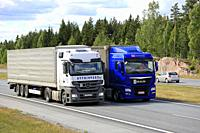 Blue MAN semi truck overtakes another truck on motorway in summer. Trucks with heavy cargo can be much slower uphill. Salo, Finland - June 8, 2018.