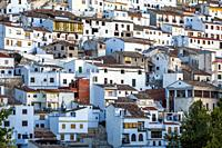 Houses and roofs next to mountain limestone, view to the mountains of the river Jucar, take in Alcala del Jucar, Albacete province, Spain.