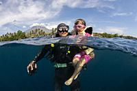 Mother with diving equipment and child with life jacket (both model released) in sea with Mt Agung volcano in background, Tulamben, east Bali, Indones...