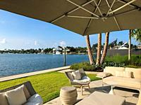 Patio furniture in backyard of house with water view, Key Biscayne, Florida, USA.