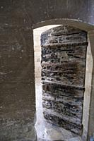 Ancient wooden door with burn marks, iron rivets and bolts, opening onto a cell in the prison block of Chartreuse Monastery, Villeneuve-les-Avignon, P...
