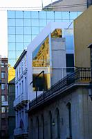 Building with mirror glass windows in a street of Alicante, Valencia, Spain