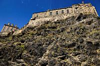 Volcanic plug cliff face of Castle Rock with red Valerian and Great Hall of the Royal Palace of Edinburgh Castle with blue sky in Edinburgh Scotland.