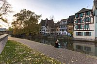 A tourist sitting by the canal in the Petit France, Strasbourg district, Alsace, Grand Est region, Bas-Rhin, France.