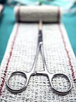 Surgical scissors on a bandage, conceptual image.