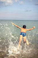Boy jumps into the sea.