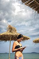 Teenage girl in bikini looking at her phone on the beach.