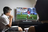 UK, London-Boy, 11 years old snacking and watching football match on TV.