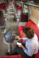 Business Woman Working on Laptop and Smartphone in First Class in a Train in Switzerland.