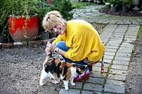 A pretty 42 year old blond woman petting a cat in a garden setting.
