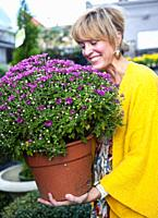 A pretty 42 year old blond woman shopping at a garden store holding a large potted chrysanthemum plant.