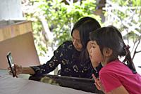 young woman and a little girl playing with a smartphone, Lasem, Java island, Indonesia, Southeast Asia.