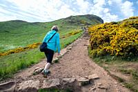 A woman walks up a path to Arthurs Seat (Holyrood Park) in Scotland.