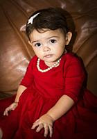 girl, 1 1/2 year old in red dress with pearl necklace.