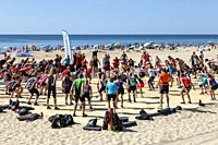 People exercising as a group on the public beach at Monte Gordo, Algarve, Portugal.