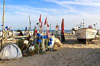 Local fishing boat surrounded by fishing floats on the beach at Monte Gordo, Algarve, Portugal in the evening sun.