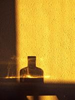 Bottle reflection over wall under sun rising light. Barcelona province, Catalonia, Spain.