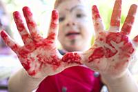 Chid boy showing his red stained hands after arts workshop for children. Closeup.