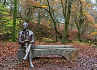 Statue of poet Robert Burns sits on bench during autumn at the Birks O'Aberfeldy scenic area in Aberfeldy, Perthshire, Scotland,UK.