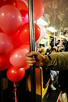 Stockholm, Sweden A man carries dozens of balloons onto the subway.