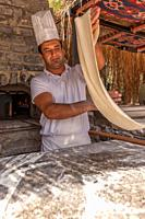Turkish pide baker baking pide for tourists at an outdoor kitchen at the beach. Near Bodrum, Turkish Riviera,Turkey,Eurasia,.