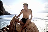 man sitting on rock at beach. At Agriomandra, Crete, Greece.
