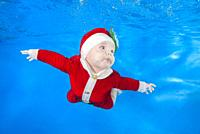 Little baby boy dressed as Santa swim underwater. Baby swimming underwater in the pool on a blue water background. Healthy family lifestyle and childr...