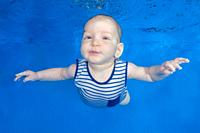 Little boy in a striped suit swim underwater on a blue water background. Healthy family lifestyle and children water sports activity. Child developmen...